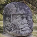 """Kolossalkopf (""""Kopf Nr. 1"""") mit der typisch helmartigen Kopfbedeckung. Das aus Basalt gehauene Moni ment stammt aus La Venta und hat einen Umfang von etwa 6 m sowie ein Gewicht von über 20 Tonnen. Au< zu dieser Kultstätte lag der nächste Steinbruch mehr als 100 km weit entfernt. La Venta-Kultur, südliche Gol küste. Etwa 500 v. d. Z. - 200 n. d. Z. Höhe: etwa 260 cm. Park-Museum, Villa Hernosa, Tabasco."""