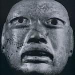 Maske aus Grünstein mit weit geöffneten Augen und Mund. Möglicherweise als Pektoral oder Gürte schmuck getragen. Ursprünglich waren auch hier, wie bei allen altmexikanischen Masken, die Augen m anderem Material eingelegt. Im Stil der La Venta-Kultur, südliche Golfküste. Etwa 600 v. d. Z. - 200 n. d. i Höhe: 14,5 cm. Museo Nacional de Antropologia, Mexiko D.F.