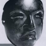 Maske aus schwärzlichem Stein. Vermutlich als Pektoral oder Gürtelschmuck getragen. Herkunft südliches Veracruz. La Venta-Kultur, südliche Golfküste. Etwa 500 v. d. Z. - 200 n. d. Z. Höhe: 8 cm. Sammlung Robert J. Sainsbury, London.