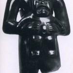 """Hochpolierte Figur eines Stehenden mit vorgehaltenem Kind aus dunkelgrüner Jade. Die Gesichtszüj Kindes weisen die Attribute einer Jaguarmundpartie auf. In der Archäologie wird dieser Typ mit """"jaguar bezeichnet. Fundort unbekannt, jedoch kann diese Skulptur als ein reines Beispiel der La Venta-Kultur v< südlichen Golfküste angesehen werden. Etwa 500 v. d. Z. - 200 n. d. Z. Höhe: 21 cm. Brooklin Museum, New York. Leihgabe: Mr. und Mrs. A. B. Martin (Guennol Collection)."""