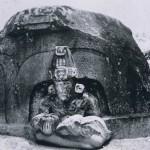 """Vorderansicht des """"Altars B"""" (vergleiche Abb. 24) zeigt eine plastisch herausgearbeitete Priesterfigi einer für die La Venta-Kultur typischen Nische sitzend. In den Armen hält die dargestellte Person ein Möglicherweise handelt es sich um eine Opfergabe an eine Vegetationsgottheit. Fundort: La Venta. La V Kultur, südliche Golfküste. Etwa 500 v. d. Z. - 200 n. d. Z. Höhe: 107 cm. Park-Museum, Villa Hermosa, Tabasco."""