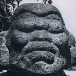 Basaltfigur eines auf dem Bauch liegenden Menschen. Der Kopf ist ausgearbeitet, während der Körper nach hinten in einen rechteckigen Block verläuft und nur noch umrißhaft angedeutet ist. La Venta-Kultur, mittlere Golfküste. Etwa 500 v. d. Z. - 200 n. d. Z. Höhe des Kopfes: etwa 80 cm. Länge: 150 cm. Auf dem Marktplatz in Tuxtla Santiago, Veracruz.