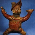 Sitzender, buckliger Musikant mit weit ausgebreiteten Armen. In einer Hand hält er den Klangkörper (Muschel), in der anderen das Schlaginstrument (Knochen). Rötlich-braune Bemalung. Fundort unbekannt. Kultur der Nordwestküste, Colima-Stil. Etwa 300-1000 n. d. Z Höhe: 32,5 cm. Southwest Museum, Los Angeles, USA