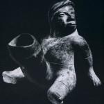 """Skulptur eines sitzenden Mannes aus rötlich bemaltem Ton. Solche phallischen Darstellungen sind si in der Kunst des alten Mexiko. Aus Tlatilco sind einige bekannt, die vermutlich als Fruchtbarkeit gedacht waren. Bei den phallischen Skulpturen der Nordwestküste, die viele Jahrhunderte später ei sind, scheint es sich jedoch mehr um """"Karikaturen"""" zu handeln, denn es ist schwer denkbar, daß hint übertriebenen Darstellungen gefestigte religiöse Vorstellungen gestanden haben. Solange aber das reiche Material, das nur aus dieser Gegend stammt, von Wissenschaftlern noch nicht gesichtet ist, kö Vermutungen angestellt werden. Der Fundort ist unbekannt. Kultur der Nordwestküste. Colima-S 300-1000 n. d. Z. Höhe: 20,5 cm. Sammlung Dr. Kurt Stavenhagen, Mexiko D.F."""