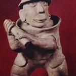 Mit Keule bewaffneter Krieger. Zu seinem Schutz trägt er einen Helm, Brustpanzer und einen schürz. Ockerfarbener Ton. Fundort unbekannt. Kultur der Nordwestküste, Nayarit-Stil. Etwa 300—10C Höhe: 44 cm. Museo Nacional de Antropologia, Mexiko D.F.