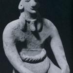 Sitzende Frauenfigur mit Lendenschurz bekleidet. Als Halsband trägt sie ein Amulett in Form eir kopfes. Kompakter, unbemalter Ton. Fundort unbekannt. Kultur der Nordwestküste, Colima-Stil. Etwa 300 bis 1000 n. d. Z. Höhe: 14,8 cm. Münchner Privatsammlung.