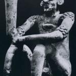Gefäß in Form eines sitzenden Mannes aus weißlich bemaltem Ton. Die stark stilisierte erhobene Hand dient als Ausguß. Auf den Schultern und an den Oberarmen ist eine Narbentatauierung zu erkennen. Fundort unbekannt. Kultur der Nordwestküste, Colima-Stil. Etwa 500-1000 n. d. Z. Höhe: 37 cm. Sammlung Dr. Kurt Stavenhagen, Mexiko D.F.