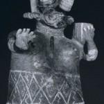 Weibliche Figur mit abweisender Geste. Auf ihrer linken Schulter trägt sie einen Topf. Wie bei den meisten Keramiken im Nayarit-Stil, so ist auch hier das Muster des Hüfttuchs polychrom aufgemalt. Rötlich grundierter Ton mit weißlicher, schwärzlicher und gelber Bemalung. Herkunft: Ixtlan del Rio Region. Kultur der Nord¬westküste, Nayarit-Stil. Etwa 300-1000 n. d. Z. Höhe: 32 cm. Galerie Wels, Salzburg