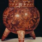 """Polychromes Dreifußgefäß, im Stil der mixtekischen Bilderschriften bemalt. Im Dekor des Halsteils ist die Glyphe atl-Wasser zu erkennen. Auf der Wölbung des Gefäßes befindet sich eine mythische Szene. Quetzalcoatl in der Maske des Windgottes und als Schöpfer des Lebens sowie Tonacatecuhtli, """"der Herr unseres Fleisches"""", nehmen den Mittelpunkt der Darstellung ein. Ihnen gegenüber ist ein Tempel oder eine kultische Anlage, die zu den Gottheiten in Beziehung steht, in starker Stilisierung wiedergegeben. Nachklassische Zeit. Mixtekische Kultur. Fundort Nochistlan, Mixteca Alta, Oaxaca. Etwa 1200-1450. Höhe: 18 cm. Museo Nacional de Antropologia, Mexiko D.F."""