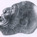 Flacher Kopf eines Mannes aus dunkelgrünem Gestein. Die Wangen sind eingefallen. Die Zunge ist etwas herausgestreckt. Möglicherweise handelt es sich um das Abbild eines Toten. Fundort unbekannt. Kultur der mittleren Golfküste, Tajin-Kultur. Etwa 500-1200. Höhe: 18,5 cm. Museum für Völkerkunde, Wien.