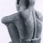 """Figur des Gottes Ixtlilton """"kleines Schwarzgesicht"""" (Rückansicht). Der Gott ist nur mit einem Lendenschurz bekleidet. Die feine Ausarbeitung der Schulterpartien zeigt die große künstlerische Ausdruckskraft des ano¬nymen Bildhauers. Jede Einzelheit an diesem Stück ist mit großer Sensibilität gesehen und gestaltet. Herkunft: Hochtal von Mexiko. Aztekische Kultur. Etwa 1450-1521. Höhe: 45 cm. Museum für Völkerkunde, Basel (Sammlung Lukas Vischer)."""