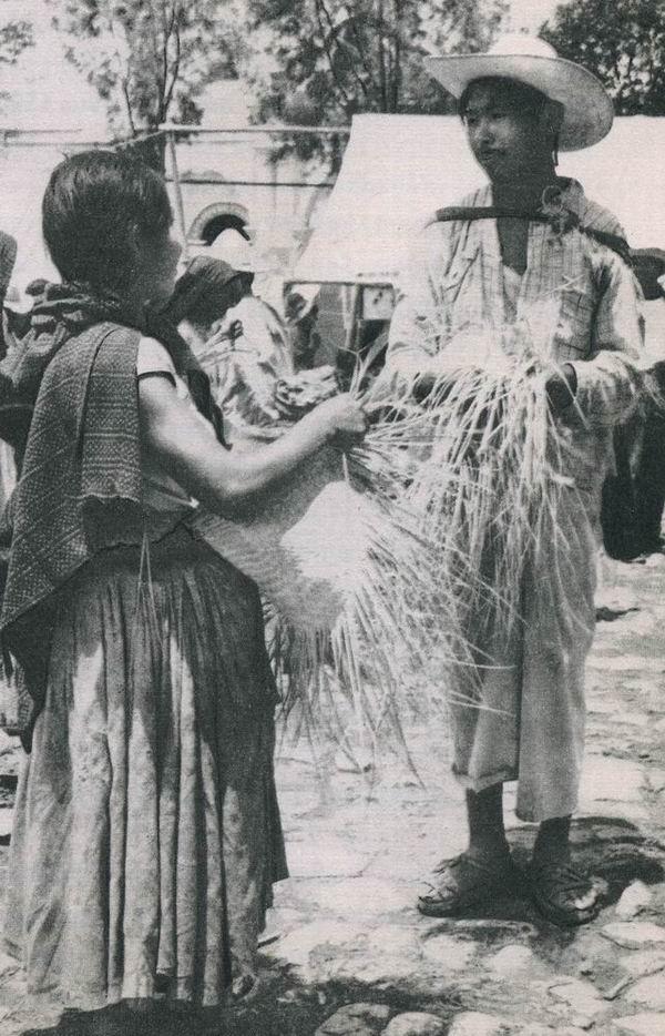 """Junges mixtekisches Paar auf dem Markt in Chalcatongo (Mixteca Alta). Das Flechten von Strohhüten ist die einzige """"Industrie"""" in diesem Hochland und jedermann ist darauf angewiesen, etwa täglich einen Hut zu fertigen, um dafür von reisenden Händlern Mais zu tauschen, denn die Ernten reichen für die Ernährung der Bevölkerung nicht aus. Der Preis für einen Strohhut beträgt umgerechnet etwa den Wert von 15 Pfennigen"""
