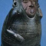 Schwarzes, poliertes Tongefäß in Form eines auf seinen Fersen sitzenden fetten Mannes. Sein Helm hat die Form eines Entenkopfes. Fundort Tlatilco, Hochtal von Mexiko. Vorklassische Zeit. Etwa 1300-700 v. d. Z. Höhe: 24 cm. Privatsammlung Mexiko D.F.