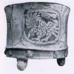 Dreifußgefäß mit einem grünlichen Stuckmantel überzogen (in der sogenannten Cloisonne-Technik deko¬riert). Das teils geritzte, teils geschabte Dekor zeigt vier stilisierte Adler. Unten läuft ein Fries mit plastisch her¬vortretenden Götterköpfen, die mit Hilfe von Formen vor dem Brennen in den weichen Ton gepreßt wurden. Herkunft: Hochtal von Mexiko. Klassische Periode. Teotihuacan-Kultur. Etwa 500-800 n. d. Z. Höhe: 18,5 cm, Durchmesser: 21,5 cm. Brooklin Museum, New York, USA.