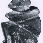 Zeremonialaxt in Form einer sitzenden Figur aus grau-grünem Gestein. Herkunft: Region von Mezcala, Guerrero. Mezcala-Stil. Ohne genaue Zeitangabe (vermutlich zwischen dem 1. und 8. Jahrhundert). Höhe: 14 cm. Sammlung J. C. Leff, Uniontown, USA.