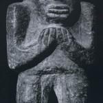 Stehende Figur mit an die Brust gepreßten Händen. Grauer massiver Stein. Herkunft: Hochtal von Oaxaca. Vorklassische Zeit (Monte Alban I). Etwa 500-200 v. d. Z. Höhe: 30 cm. Museo Frissell de Arte Zapoteco, Mitla, Oaxaca