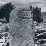 """Ein sogenannter """"Danzante"""" (Tänzer) auf dem Monte Alban. Diese affenartigen, grotesk anmutenden Figuren sind im leichten Relief in künstlich abgeplattete Steine gemeißelt. Die Monumente tragen die ältesten Schriftzeichen, archaische Glyphen, die noch nicht entziffert werden konnten. Vorklassische Zeit (Monte Alban I). Etwa 500-200 v. d. Z. Höhe: 119 cm. Monte Alban, Oaxaca"""