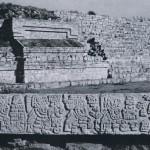 """Fragment eines zapotekischen """"Altars"""" auf dem Monte Alban. Vier Häuptlinge, im Relief dargestellt, wer¬den von einem Priester oder Fürsten empfangen. Die Namens- oder Ortshieroglyphen befinden sich oberhalb der Figuren. Späte zapotekische Kultur (Monte Alban IV). Etwa 700-900 n. d. Z. Länge: 192 cm. Monte Alban, Oaxaca"""