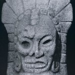 """Steinmonument in Form einer """"Palma"""" zeigt eine Figur mit gespaltenem Gesicht. Eine Hälfte gibt de Leben, die andere den Tod wieder. Fundort unbekannt. Kultur der mittleren Golfküste, Tajin-Kultur. Etw 500-1200. Höhe: 40 cm. Sammlung Dr. Kurt Stavenhagen, Mexiko D.F."""