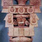 Polychromes Tongefäß in Form eines stilisierten Tempels. Im Mittelpunkt ist ein menschliches Antlitz zu sehen, das eine uns unbekannte Gottheit repräsentiert. Die Azteken hatten in ihrer Keramik keine eigene Tra¬dition. Um nicht weitere Verwirrung zu stiften, unterteilt die Archäologie die Keramik des gesamten Hochtals in vier verschiedene Phasen: Aztekisch I mit dem Ursprung in Cholula und Puebla. Die Keramik ist stark mixtekisch beeinflußt, möglicherweise sogar Zeugnis dieses Kulturvolkes selbst. Die Zentren der Herstellung im Hochtal von Mexiko lagen besonders in Colhuacän, das in direkter Verbindung zur Mixteca-Puebla-Kultur stand, sowie in Mazapan und Coyotlatelco. Aztekisch II mit dem Mittelpunkt in Tenayuca, ein kultisches Zentrum, das bereits vor dem Eintreffen der Azteken im Hochtal von Mexiko aktiv war.  Aztekisch III und IV ist ein Konglomerat von vielen Strömungen im Hochtal. Erst in dieser Phase kann man die Keramik als rein aztekisch bezeichnen. Herkunft des abgebildeten Gegenstandes: Azcapotzalco. Einflüsse der Teotihuacan-Kultur sind bei diesem Objekt noch deutlich sichtbar. Nachklassische Periode. Etwa 1200-1400.  Höhe: 60 cm. Museo Nacional de Antropologia, Mexiko D.F.