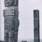 """Einer der """"Atlanten"""" in Tula. Die Dachträger repräsentieren vermutlich Quetzalcoatl als Morgenstern¬gott, der auf dem Rücken die Sonnenscheibe trägt. Im Hintergrund eine Säule mit dem Relief einer Kriegerfigur; ein neues Thema, dem militanten Geist dieser Kultur entsprechend. Nachklassische Zeit. Toltekische Kultur. 900-1168. Höhe: 480 cm. Tula, Hidalgo."""