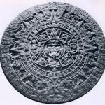 """Der """"Kalenderstein der Azteken"""" aus Basalt mit einem Gewicht von etwa 24 Tonnen. Im Zentrum die Sonne, umgeben von den Glyphen der vier vorhergegangenen Sonnen-Zeitalter: """"Windsonne"""", """"Feuersonne"""" """"Regensonne"""", """"Wassersonne"""". Um diese Symbole bildet sich ein Kreis mit den 20 Tageszeichen des mexikani sehen Kalenders. Ornamental angeordnet, folgt ein weiterer Kreis von stilisierten Sonnenstrahlen-Zeichen, di« die Jahre anzeigen. Eingerahmt wird die Darstellung von zwei Feuerschlangen (Xiuhcoatl), Symbole der Zei und des Raums. Zwischen den Schlangenleibern findet sich das Kalenderzeichen 13 Rohr, das unserem Jahi 1479 entspricht und vermutlich das Weihedatum dieses gewaltigen Monuments anzeigt. Gefunden wurde diesei Stein auf dem Hauptplatz von Mexiko-Stadt. Das Rohmaterial dafür ist vom Festland herbeigeschafft worden Nach der Eroberung stürzten die Spanier die alten Idole in die Kanäle. Schlamm und Schmutz verbarg sie für Jahrhunderte. Erst mit der Modernisierung des alten Stadtkerns kamen einige Monumente wieder ans Tages¬licht. Unzähliges aber liegt noch unter der modernen 5,5-Millionen-Stadt begraben. Nachklassische Zeit, Aztekische Kultur. 1479? Durchmesser: 360 cm. Museo Nacional de Antropologia, Mexiko D.F."""